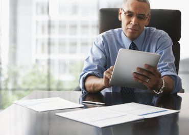 Businessman looking over electronic tablet